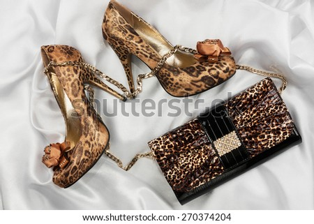 Leopard bag and shoes  lying on white  fabric, can use as background - stock photo
