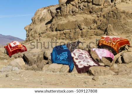 LERIBE, LESOTHO - AUGUST 10, 2016: Modern Basotho blankets dry in the sun after being washed on a winter afternoon in rural Lesotho; blankets are worn for fashion and warmth in this mountainous nation