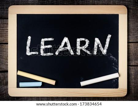 Lern handwritten with white chalk on a blackboard on wooden background  - stock photo