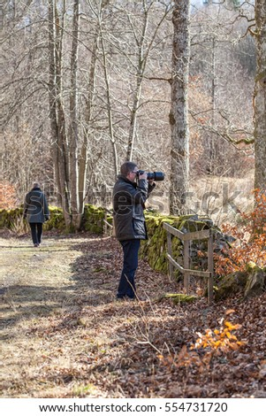LERUM, SWEDEN, MARCH 2015, an older, Swedish couple out in nature on a sunny spring day. Husband taking photographs.