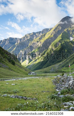 LES CHAPIEUX, FRANCE - AUGUST 27: Mountains chain with lonely chalet at the hill side. The region is a stage at the Mont Blanc tour, which crosses three countries. August 27, 2014 in Les Chapieux. - stock photo