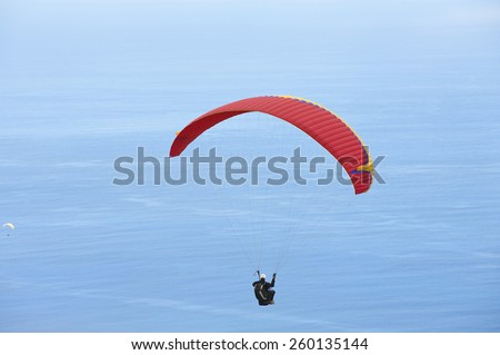 LES COLIMATONS LES HAUTS DE REUNION, FRANCE - DECEMBER 04, 2010: Unidentified paragliders fly over Indian ocean on December 04, 2010 in Les Colimatons Les Hauts De Reunion, France. - stock photo