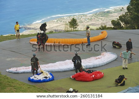 LES COLIMATONS LES HAUTS DE REUNION, FRANCE - DECEMBER 04, 2010: Unidentified paragliders get ready to fly on December 04, 2010 in Les Colimatons Les Hauts De Reunion, France. - stock photo