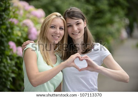 lesbian couple forming heart shape with hands - stock photo