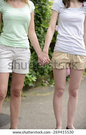 Lesbian couple holding hands outdoors - stock photo