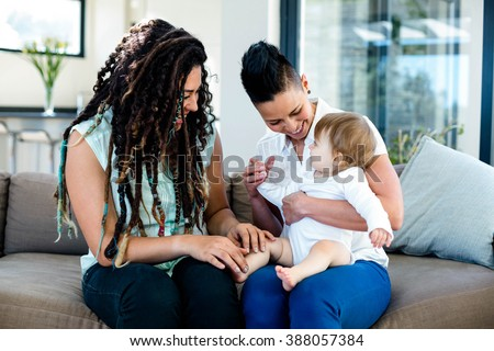 Lesbian couple playing with their baby in living room - stock photo
