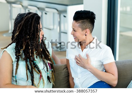 Lesbian couple talking to each other in living room