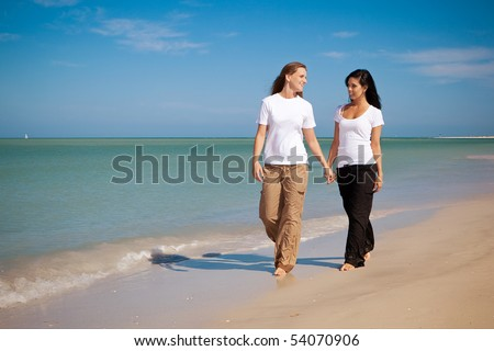 Lesbian couple walking on beach, holding hands - stock photo