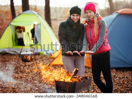 lesbian girls are heated by the fire on a background of playing children - stock photo