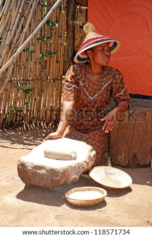 LESEDI,SOUTH AFRICA - JAN 1:Sotho woman in handmade dress and conical hat cooking maize meal at tribal house on January 1,2008 at Lesedi Village, South Africa.Maize meal is basic African ingredient. - stock photo