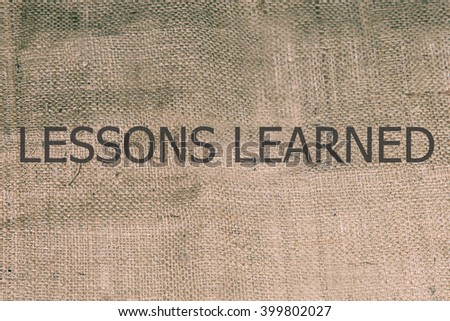 lessons learned text on brown burlap. burlap, canvas texure retro background