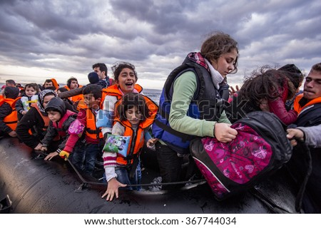 Lesvos island, Greece - 29 October 2015. Syrian migrants / refugees arrive from Turkey on boat through sea with cold water near Molyvos, Lesbos on an overload dinghy. Leaving Syria that has war. - stock photo