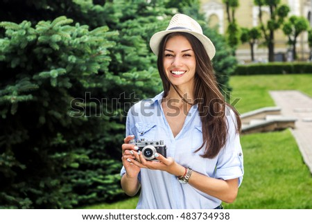 Let me capture your best moment. Shot of a young woman in a hat holding a vintage camera .