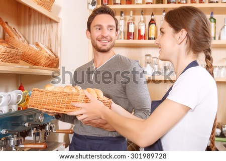 Let me help. Young handsome cafe worker is helping his female colleague to set out goods on stalls - stock photo