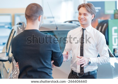 Let me tell you everything about this car. Selective focus on a young smiling sales consultant who communicates with the customer standing backward to the camera with a new car on the background - stock photo