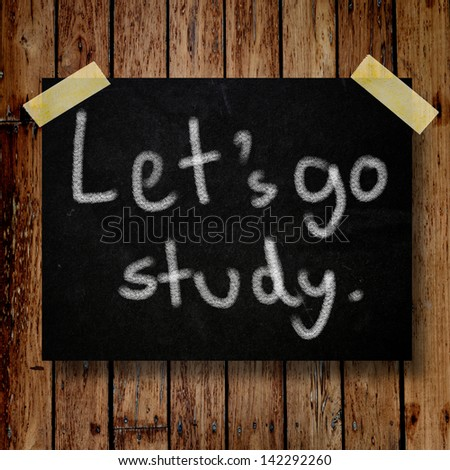 Let's go study on message note with wooden background - stock photo