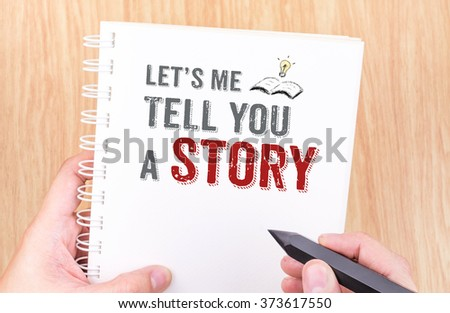 Let's me tell you a story work on white ring binder notebook with hand holding pencil on wood table,Business concept - stock photo