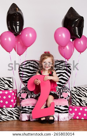 Let's Party!  Adorable little girl celebrating her second birthday.   - stock photo