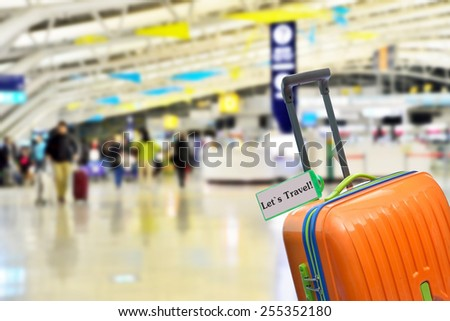 Let`s Travel! Orange suitcase with label at airport. - stock photo