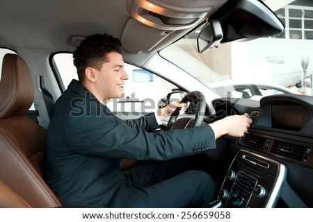Let us go for a ride. Handsome young businessman examining the car at the dealership while sitting inside the new car and touching the steering wheel - stock photo