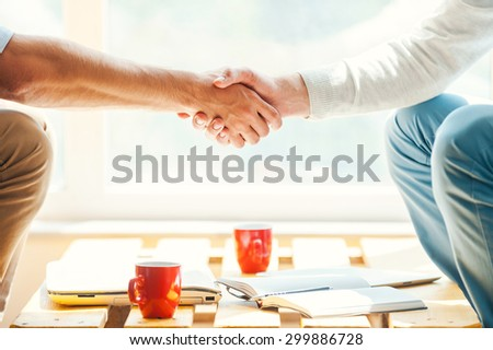 Let us shake on it! Close-up of two men shaking hands while sitting in front of the window - stock photo