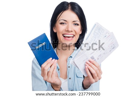 Let us travel! Beautiful young smiling woman holding tickets and passport while standing against white background - stock photo