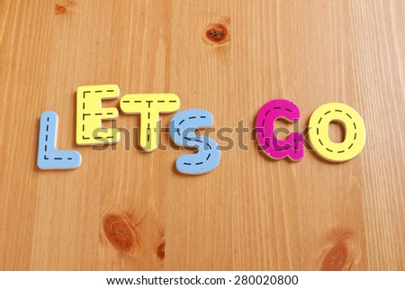 LETS GO, spell by woody puzzle letters with woody background - stock photo
