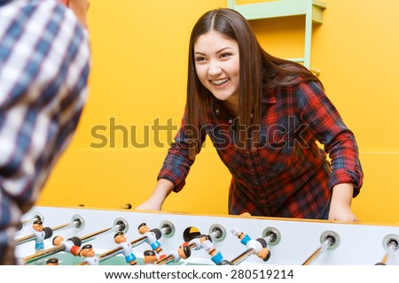 Lets play. Beautiful young Asian girl looking smiling at her partner while playing air hockey wearing checkered shirt in a yellow room