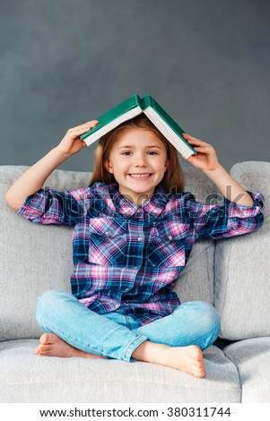 Lets play hide and seek! Cheerful little girl holding book over her head and looking at camera with smile while sitting on the couch in lotus position at home - stock photo