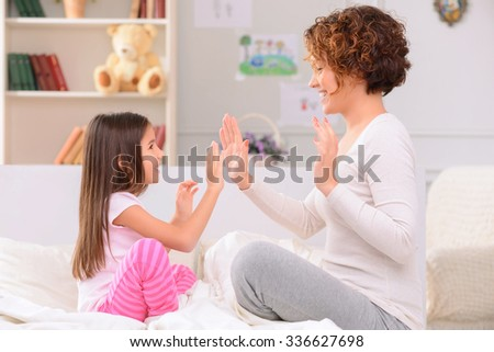 Lets play. Pleasant upbeat nice mother and daughter sitting on bed in front of each other and clapping their hands while having fun - stock photo