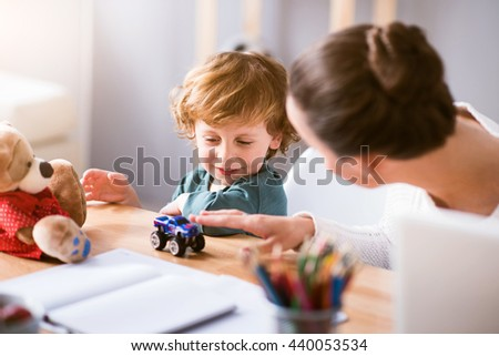 Lets play. Young mother playing with her little smiling child while sitting at the table - stock photo
