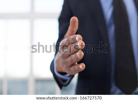 Lets shake hands! Close-up of African businessman stretching out hand for shaking