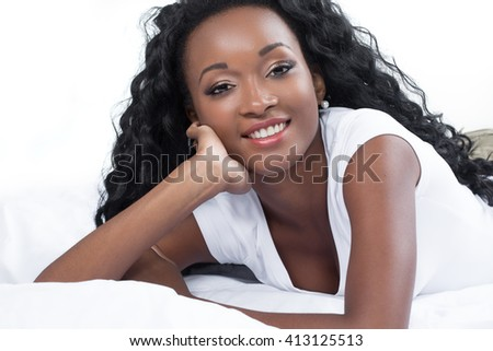 Lets start new day. Young African woman in tank top lying in bed.
