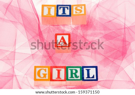 Letter blocks spelling its a girl shot on a pink background - stock photo
