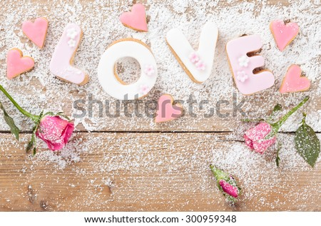 Letter cookies for Valentine's day or wedding day. On old wooden table. - stock photo