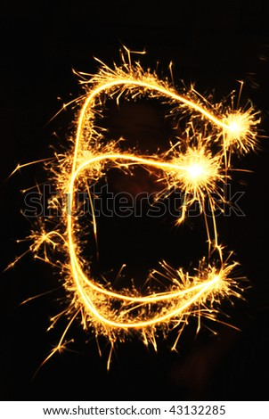Letter E made of sparklers isolated on black