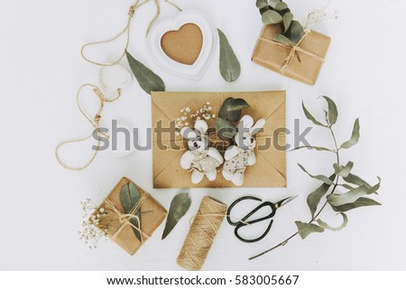 Letter, envelope and gift on white background. Invitation cards, or love letter with pink roses. Holiday concept, top view, flat lay