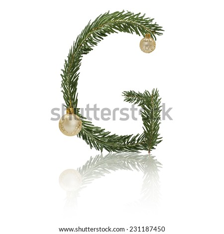 Letter G made from fir branches, decorated with christmas balls and reflection. - stock photo