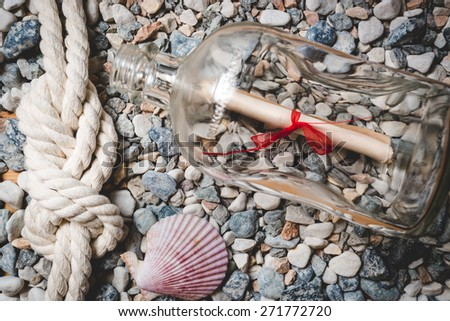 Letter in bottle lying on seashore with marine rope and seashells - stock photo