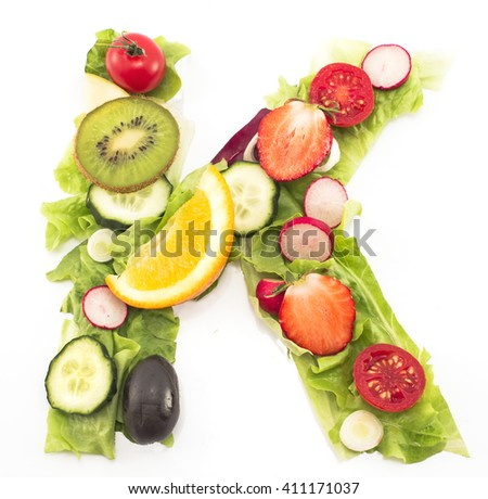 Letter K made of salad and fruits.