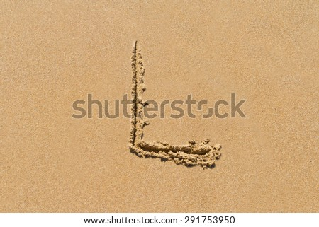 Letter L of the alphabet written on sand with upper case. - stock photo