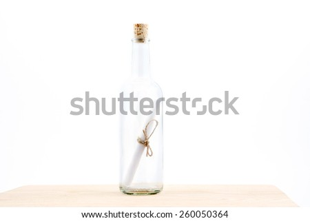 Letter or message in a bottle on a white background - stock photo