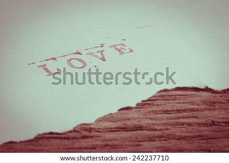 Letter stamp with word LOVE on white paper - stock photo