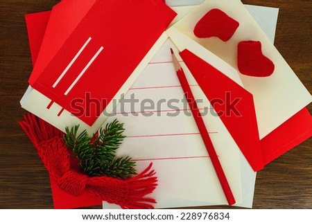 Letter to Santa Claus with envelopes, red pencil, the Christmas tree and boots on a wooden background