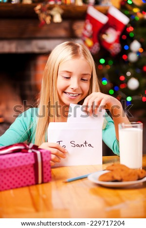 Letter to Santa. Cute little girl putting a letter to Santa into the envelope while sitting at the table with glass of milk and cookies laying on it  - stock photo