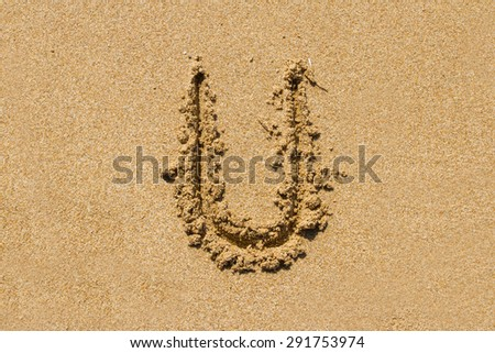 Letter U of the alphabet written on sand with upper case.