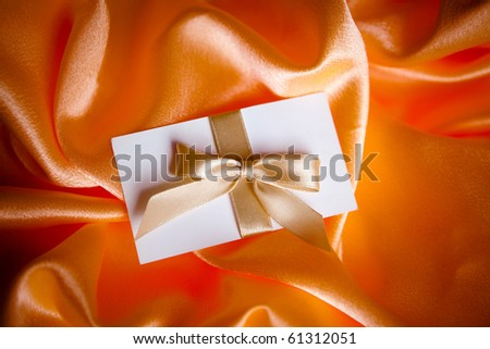 letter with golden ribbon on red satin - stock photo