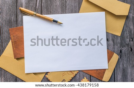 Letter with pen and envelopes on a wood table - stock photo