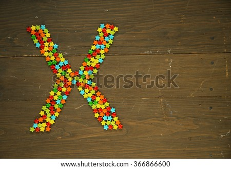 Letter X from alphabet made with star shape candy on a wooden background - stock photo