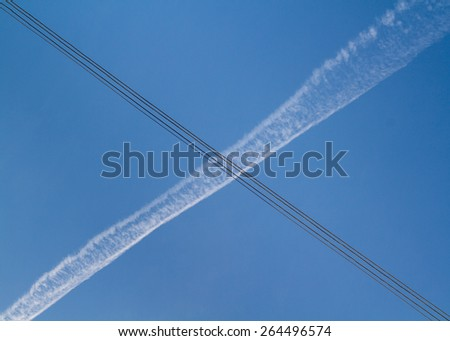 Letter X or cross, formed when the wake of a plane intersects the silhouette of an electric line - stock photo
